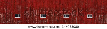 A wide barn side red painted wall that is aged and textured with 4 windows. - stock photo