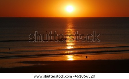 a wide beach of Normandy, France at sunset.