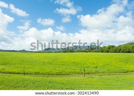 A wide expanse of green pastures and a vibrant sky in the highlands of Hawaii - stock photo