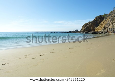 A wide scenic panorama of gently flowing ocean surf against a beautiful sandy beach in a secluded cove in Laguna Beach, California during a bright, sunny day. - stock photo