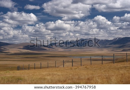 A wide steppe with yellow grass on the Ukok plateau near the border with Mongolia, under a cloudy sky on the background of mountain ranges, Altai mountains, Siberia, Russia - stock photo