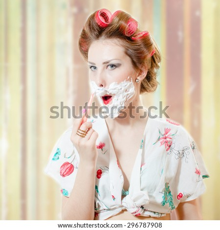 A wierd girl wearing haircurlers shaving her face with razor and foam - stock photo
