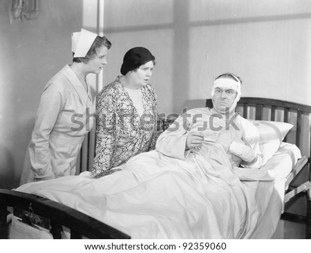 A wife next to her husband in a hospital bed with a nurse attending