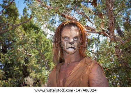 A Wild Lion man stares cautiously at the camera with a background of forest.  This is the fantastic make-up done by Rayce Bird. - stock photo