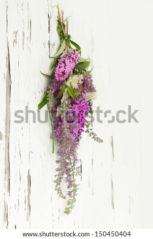 A wildflower bouquet on an old weathered door with white copy space - stock photo