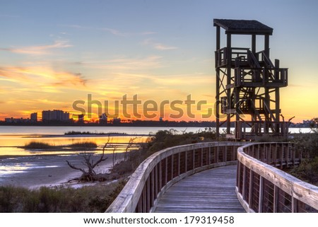 A wildlife observation tower silhouetted against a Perdido Key  sunset in Big Lagoon State Park near Pensacola, Florida - stock photo