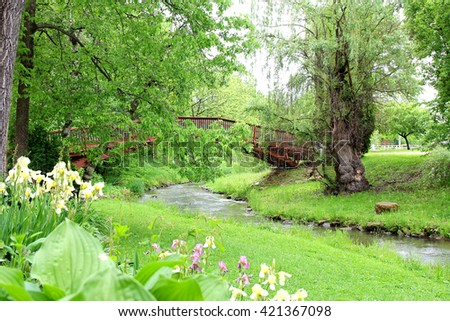 A Willow Tree, forest, hostas, and irises form a garden around a wooden walking bridge over a stream in the park.
