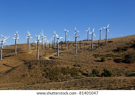 A wind farm of turbines sits on top of a hillside.