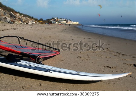 a wind surf board sits on a tropical beach with kite surfers in the background
