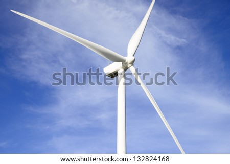 A wind turbine against a blue sky - stock photo