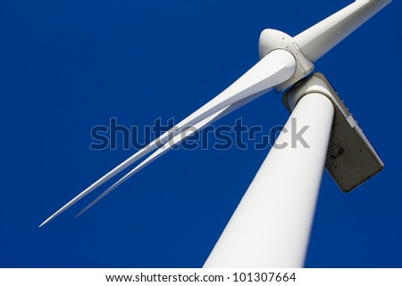 A wind-turbine against a clear blue sky - stock photo