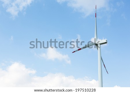 A wind turbine in front of blue sky with some clouds