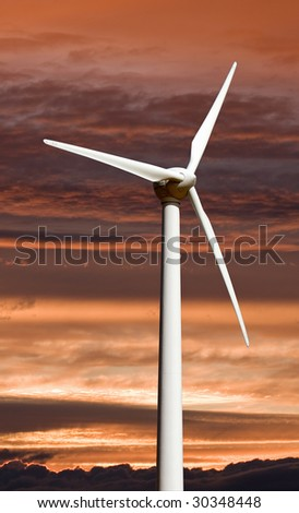 A wind turbine used for electricity generation against sunset sky. - stock photo
