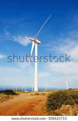 A wind turbine with a set of other turbines in the background.