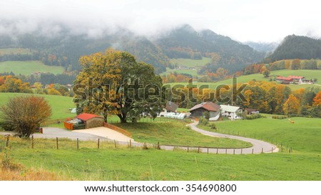 A winding country road curves between green fields and autumn trees leading to a farmhouse on a beautiful hillside ~ Scenery of romantic fall countryside in Ramsau, Bavaria Germany  - stock photo