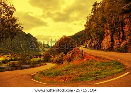 A winding country road with a steep mountain at sunset time.  - stock photo