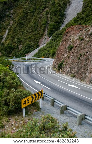 A winding road in New Zealand's South Island, an advisory road sign before the right hand turn.