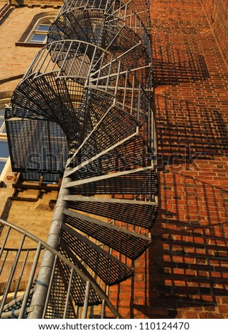 A Winding Spiral Staircase Used As Fire Escape In Old Gothic Brick Wall  Building.