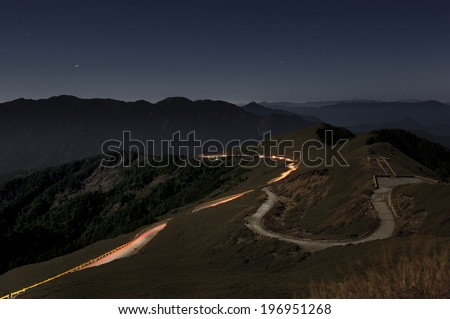 A winding trail on top of a mountain in the darkening sky. - stock photo