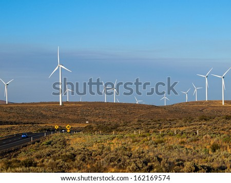 A Windmill Farm on a Mountain Beside an Interstate Highway at Dusk