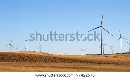 a windmill farm on a rural landscape energy conservation concept. - stock photo