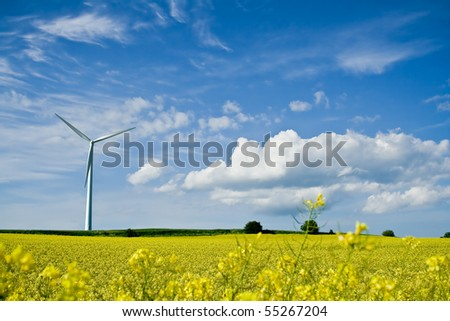 A windmill in a rapeseed field on a background of blue sky - stock photo