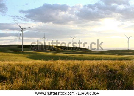 A windmill on a hillside silhouetted by a sunset - stock photo