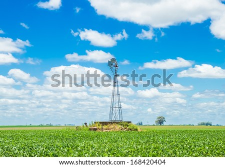 A windmill on the middle of a beautiful field under a blue sky with nice looking clouds - stock photo