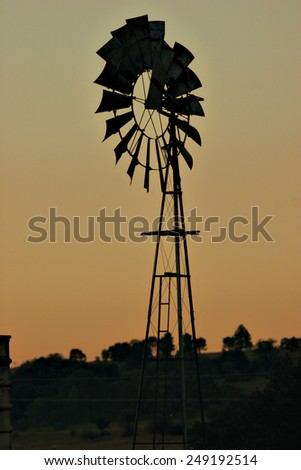 A windmill sits idly on a rural farm at sunset. - stock photo