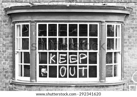 A window in a building for demolition, with warning graffiti, in black and white tones - stock photo