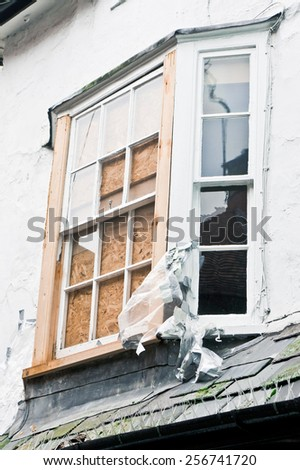 A window in an old house boarded up - stock photo