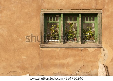 A window in the stucco of a house in Santa Fe, New Mexico