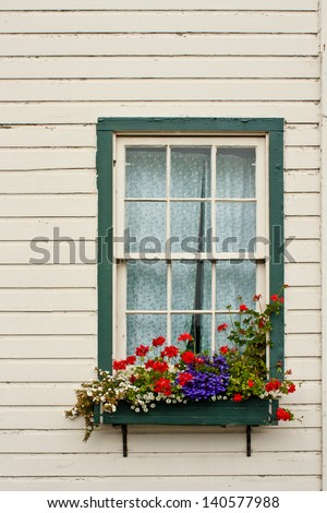 A window of an old house with a flower planter box. - stock photo