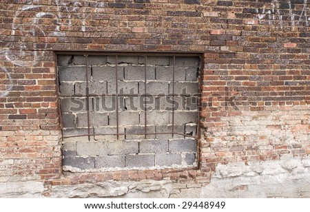 A window sealed with concrete blocks and bars on a grungy aged brick wall, background with copy space