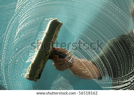 a window washer soaps up a window for window washing - stock photo