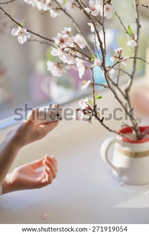 a window with a vase of flowers and hands the baby to keep the little white hamster - stock photo