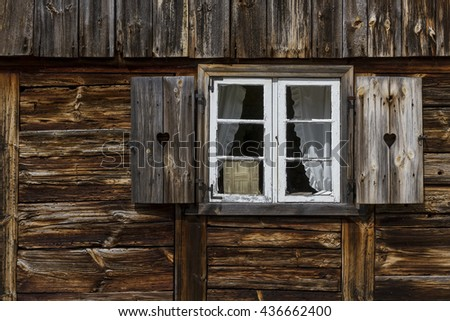 A window with shutters in old, wooden house