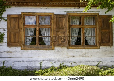 A window with shutters in old, wooden house - stock photo
