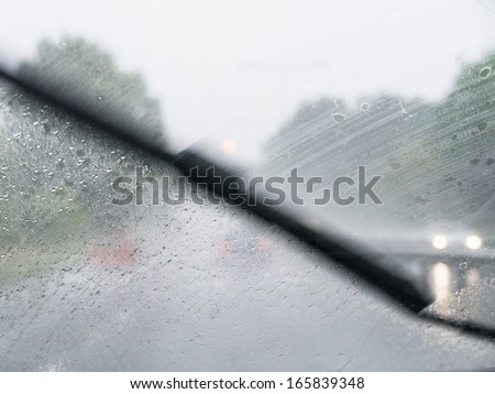 A windscreen wiper moving across a windscreen whilst a car drives on a very wet day. - stock photo