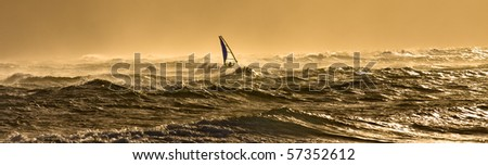 A windsurfer is riding along the beautiful Maui's shores while the sun is slowly setting on a perfect day - stock photo