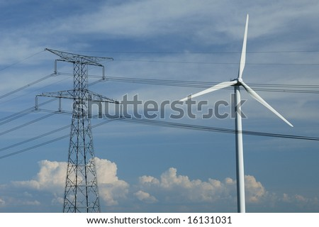 a windturbine close to a electric pylon in France - stock photo