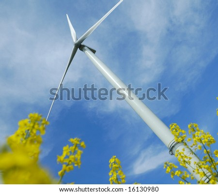 a windturbine into a yellow rapeseed field France - stock photo