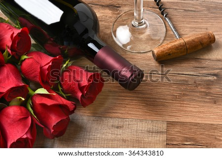 A wine bottle with red roses and a glass and cork screw on a rustic wood table. - stock photo