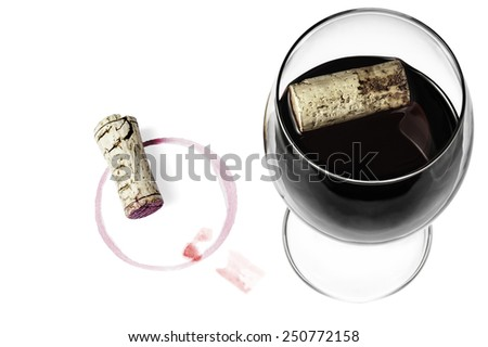 A wine glass, corks and wine imprints on a white background