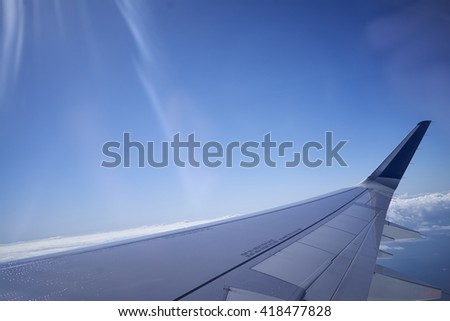 A wing of an airplane while in the air