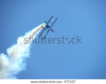 a wing walker making a shape with his hands while in flight