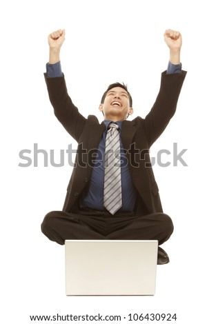 A winning businessman in front of a laptop (isolated on white)