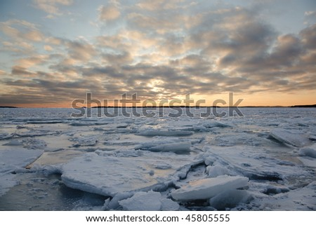A winter landscape in the sunset with packed ice in the sea. - stock photo