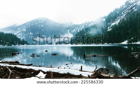 A winter landscape of distant mountains, covered in forest, surrounding a lake. - stock photo