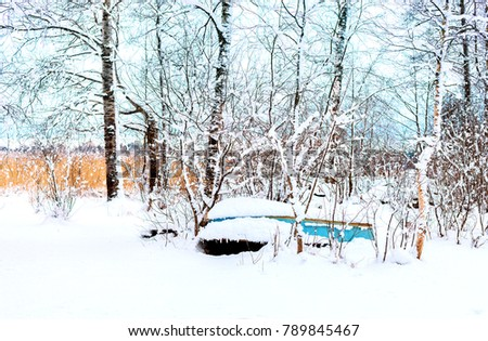 A winter landscape with the old abandoned boat on the shore, snow, winter